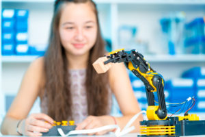 A teenager works on a robot.