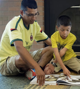 A father and son enjoy reading in the library.
